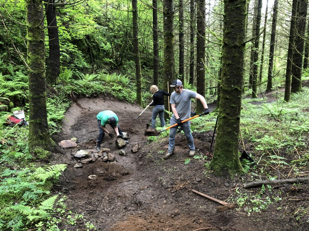The FVMBA summer trail crew of Ryan, Siobhan, and Owen working on Squid Line at Sumas Mountain