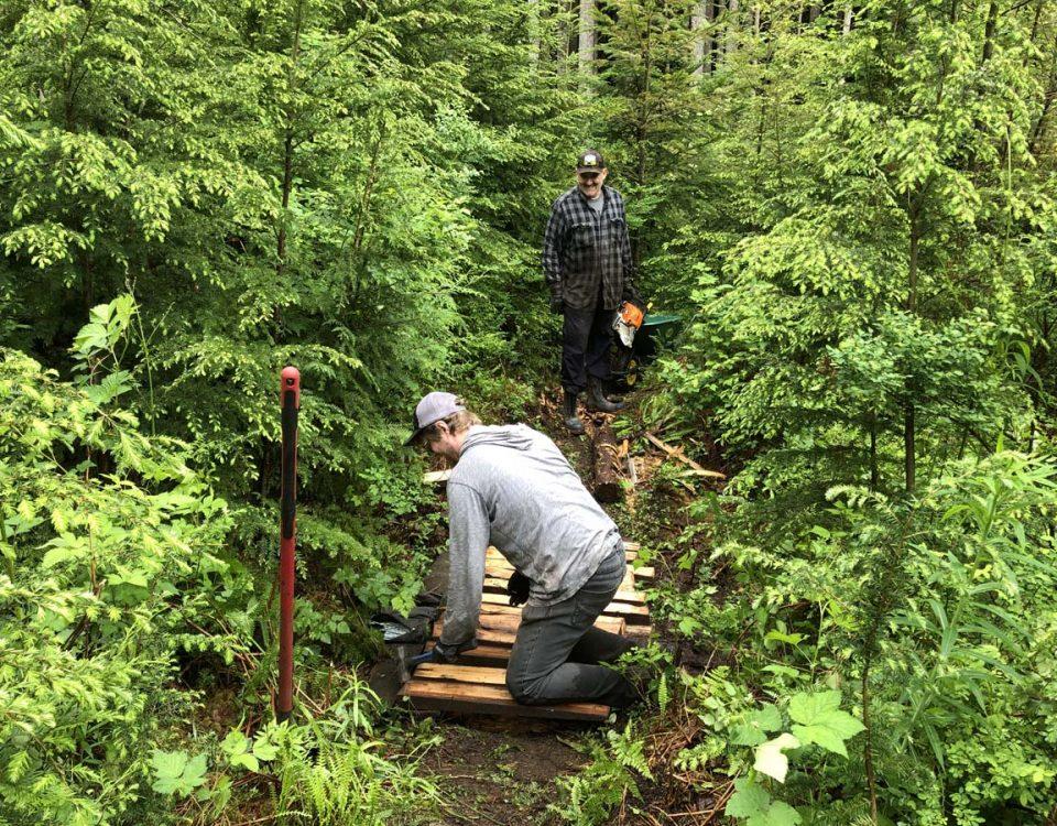 Image of Owen nailing the new bridge together while Ryan supervises