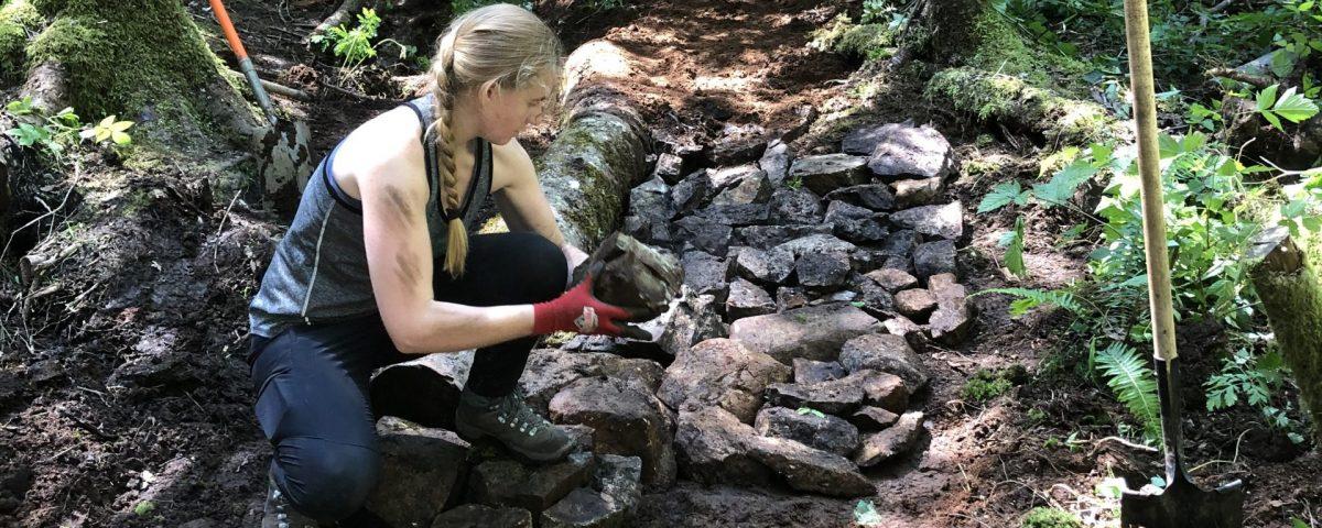 A women using rocks to repair a trail