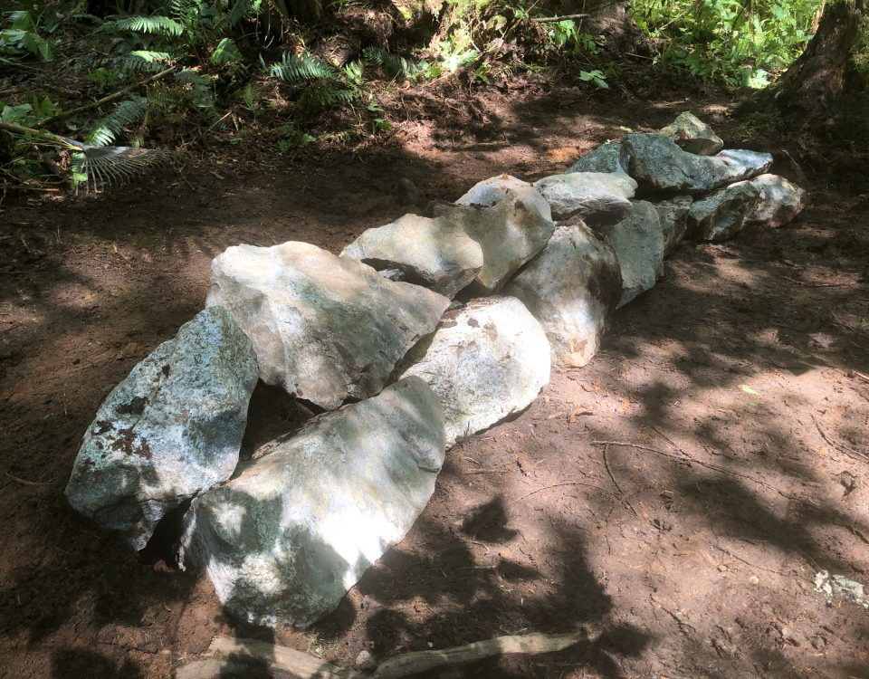 Two stacked overlapping layers of rocks form a small retaining wall that riases the height of the trail.