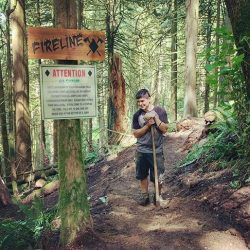 A young man leaning on a shovel on a trail in the forest next to a trail sign that says FireLine.