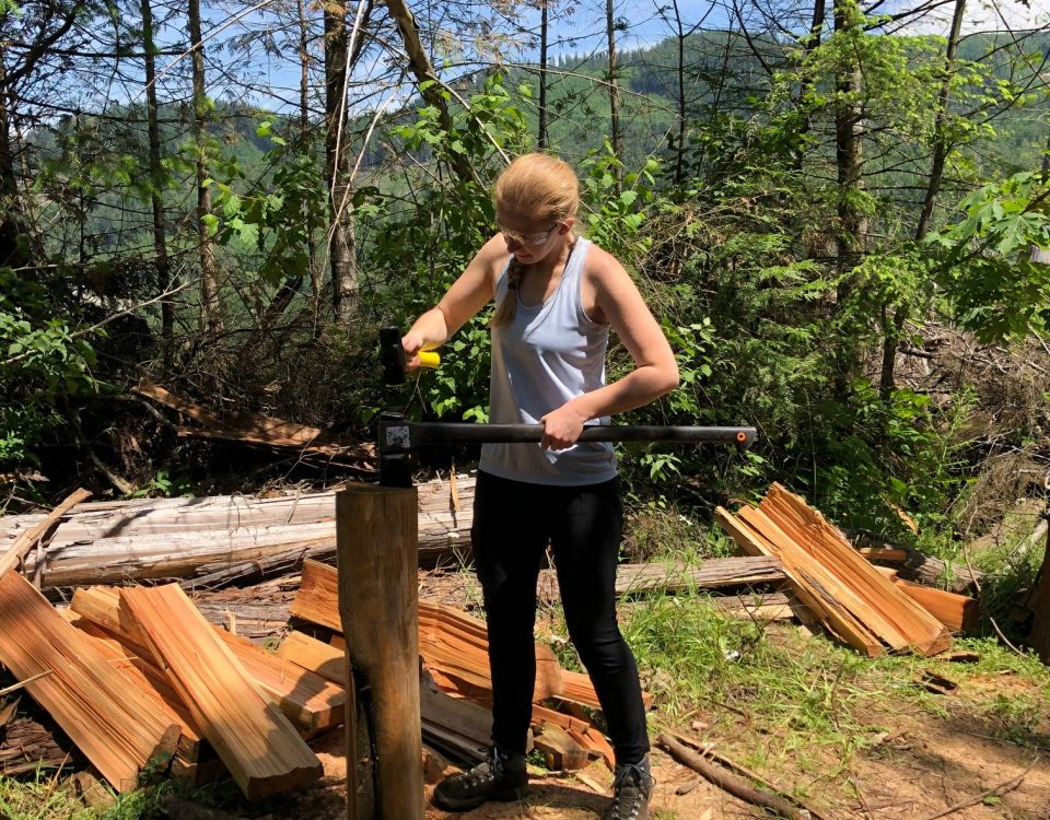 Siobhan of the FVMBA trail crew using a hammer and axe to split a cedar log into rungs to use for a bridge